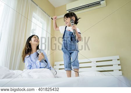 Family Relaxation Activities Concept. Her Sister And Sister Are Both Singing Karaoke. By Singing On