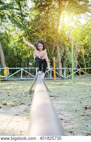 An Asian Girl Is Playing On A Playground. She Is Practicing Balance On The Metal Walkway.