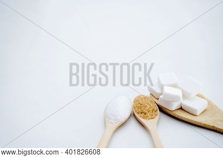 White Sugar, Brown Sugar, Sugar Cubes, Placed In A Wooden Spoon, White Background. Food Concept