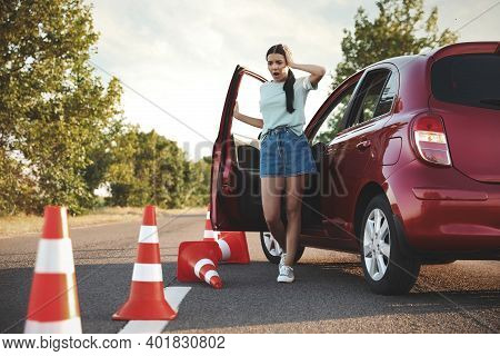 Stressed Young Woman In Car Near Fallen Traffic Cones Outdoors. Failed Driving School Exam