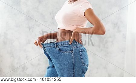 Unrecognizable Black Woman In Oversized Jeans Showing Results Of Her Weight Loss Diet Or Liposuction