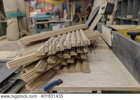 An Oak Wood Bar Blocks Materials Stacked In A Wood Joiner's Workshop With Tools And Sawdust In The B