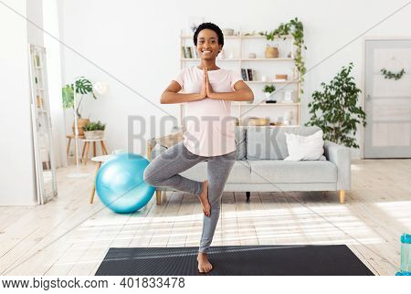 Full Length Portrait Of Expectant Young Lady Doing Her Morning Yoga Practice, Standing In Tree Pose,