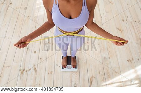 Closeup Of Slim Black Woman Measuring Her Waist While Standing On Scales At Home, Above View. Africa
