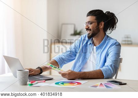 Graphic Design Courses Online. Young Arab Man Holding Colour Swatch And Using Laptop Computer At Hom