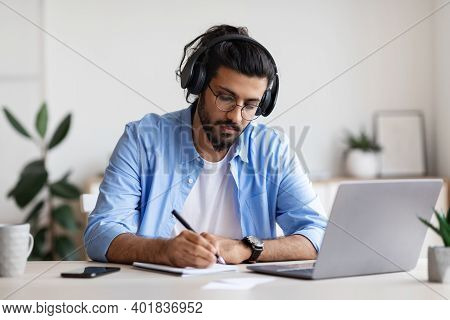 Distance Learning. Young Arab Guy In Headphones Studying With Laptop Computer At Home And Taking Not