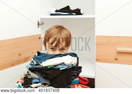 The Boy Puts Things In Order In The Closet. Order In The Closet. Wardrobe With Child's Clothing.