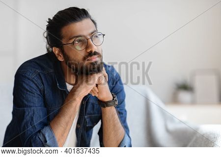 Portrait Of Thoughtful Millennial Arab Guy In Glasses Resting Head On Hands And Looking Aside, Pensi