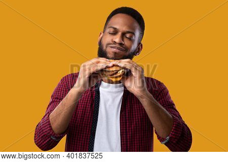 Happy African Man Eating Burger Posing Standing Over Yellow Studio Background. Black Guy Tasting Che