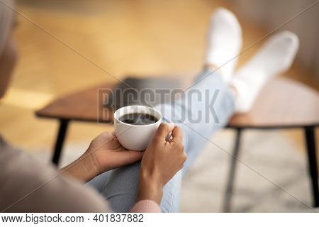 Closeup Of Young Black Woman Warming Her Hands On Cup Of Coffee, Relaxing At Home, Empty Space. Unre