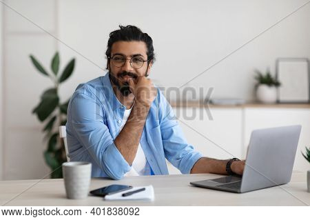 Portrait Of Smiling Young Arab Freelancer Guy Sitting At Desk In Home Office, Positive Millennial Ea