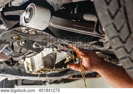 A Working Car Mechanic Unscrews The Drain Plug Of The Crankcase On The Pallet To Drain And Replace T