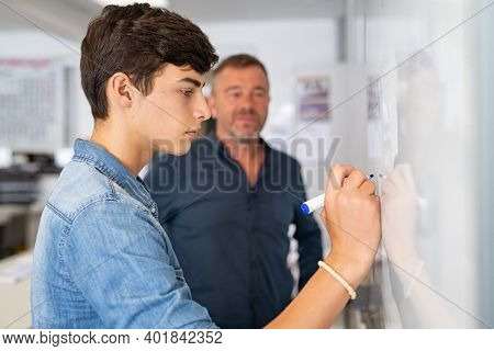 Young man writing solution of equation on whiteboard at school during math lesson with professor. College student writing on white board under the supervision of the teacher. Close up of smart guy sol