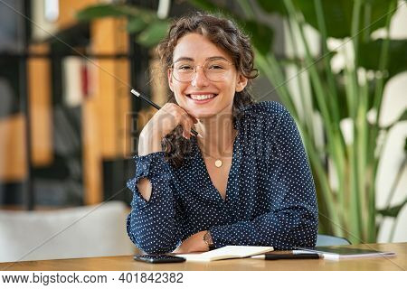 Portrait of smiling woman wearing spectacles while sitting at desk. Business woman taking notes in diary and looking at camera. University girl with eyeglasses sitting on table at library.