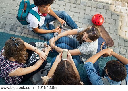 High angle view of guys and girls sitting and talking together. Cheerful group of happy friends in conversation after class. Top view of young woman using smart phone after school with classmates.