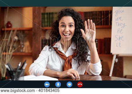Head Shot Of Smiling Young Female Teacher Waving Hand To Webcam, Greeting Students During Remote Lec