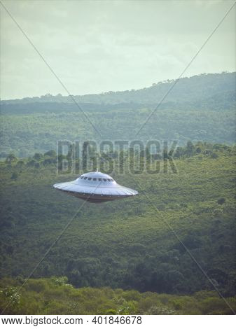 3d Illustration Of An Ufo, Unidentified Flying Object, Gravitating Over The Forest And Mountain Rang