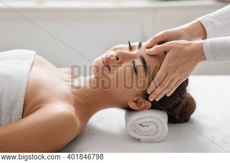 Relaxed Young Korean Lady Enjoying Acupressure Facial Massage In Spa Salon, Lying On Table With Clos