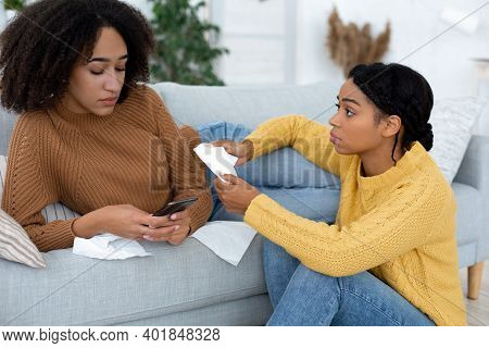 Parting, Pain, Worries And Human Emotions. Offended Young African American Female Looks At Smartphon