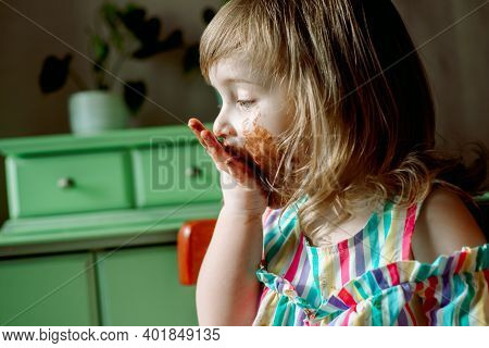 Cute Curly Redhead Baby Child Shows And Licks Hands Smeared By Chocolate.cute Girl Eats A Bell At Ho