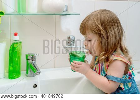 Morning Hygiene In The Bathroom. Baby The Girl Washes, Brushes Her Teeth, Rinses Her Mouth With Wate
