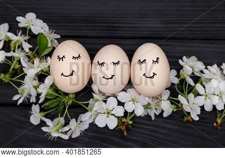 Decorative Pastel Painted Easter Eggs With Drawn Cute Face. White Blooming Cherry Branches On Black
