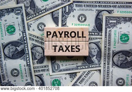 Payroll Taxes Symbol. Concept Words 'payroll Taxes' On Wooden Blocks On A Beautiful Background From