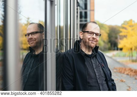 Portrait Of A Young Man Leaning Against Windows
