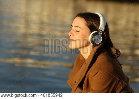 Profile Of A Woman Meditating Listening Music With Headphones In Winter On The Beach