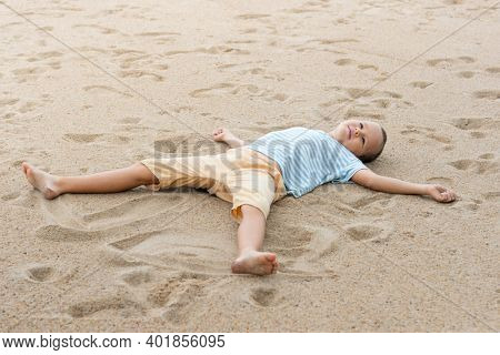 Outdoor portrait of a little cute boy laying on the sandy beach.