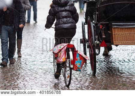 Bicycle Rider And Horse Carriage On A Rainy Day