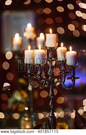 Picture Of A Candlestick With Burning Candles And Bokeh Lights In The Background