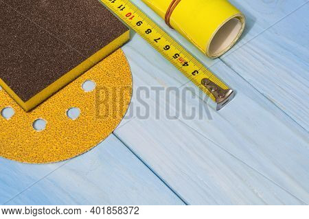 Set Of Abrasive Tool And Yellow Sandpaper On Blue Wooden Boards