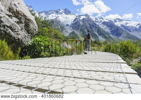 Mount Cook New Zealand - February 16 2015; Tourists Stop To Look At View On Wooden Walkway On Hooker