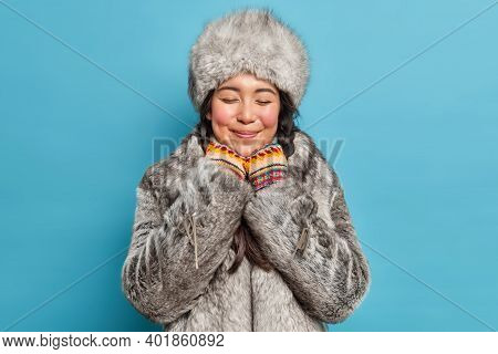 Dreamy Satisfied Young Asian Woman Closes Eyes And Smiles Gently Wears Grey Fur Hat And Coat Has Rom