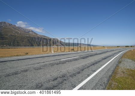 Highway Through Landscape Of Golden Grass From Highway Through Southern Alps In South Island New Zea