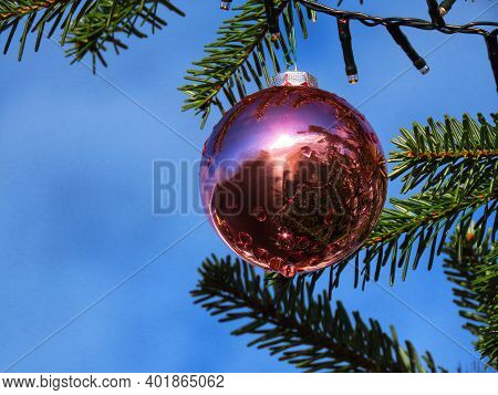 Pink Christmas Bauble Shining In Bright Sun And Green Fir Tree Branches Against Bright Blue Sky