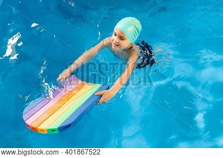 Swimming Class. Close Up Of Kids Practicing Flutter Kick With Kick Board In Swimming Pool