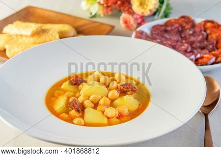 White Modern Plate With Soup Sauce, With Potatoes, Sausage Salami And Soybeans. Plates With Cheese S