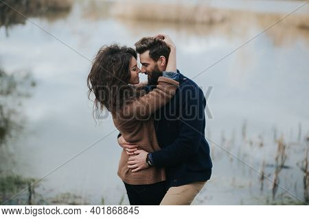 Two Caucasian Lovers Near The Lake. Young Couple Is Hugging On Autumn Day Outdoors. A Bearded Man An