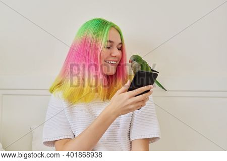 Trendy Teen Girl With Smartphone And Young Green Quaker Parrot On Her Shoulder, At Home On Bed. Pet