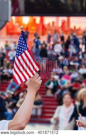 Man Holds An Us Flag In Front Of A Crowd At The Times Square In Nyc