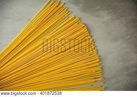 Spaghetti Lunghi Gialli Su Fondo Grigio. Pasta Sottile Disposta In File. Pasta Italiana Gialla. Spag