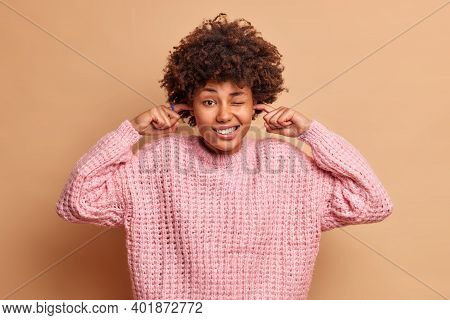 Studio Shot Of Beautiful African American Woman Clenches Teeth Plugs Ears To Avoid Loud Noise Asks T