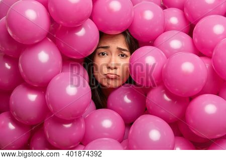 Upset Displeased Miserable Asian Woman Surrounded With Inflated Pink Balloons Has Bad Mood On Holida