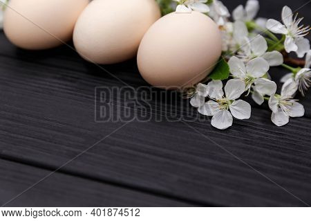Uncolored Natural Easter Eggs On Black Wooden Background. Happy Easter Concept With White Spring Flo