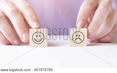 Close-up Of Person's Hand Holding Wooden Block With Happy And Unhappy Face On Reflective Desk