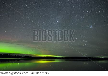 Night sky with stars and Aurora Boreal Northern lights at horizon in Finland