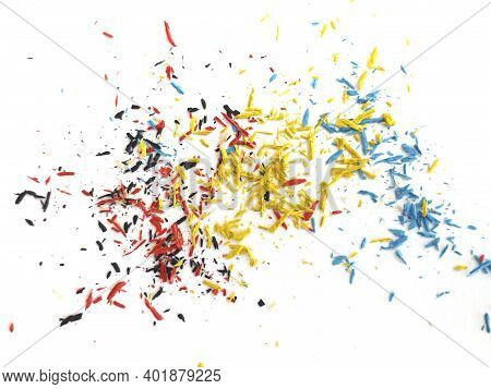 Small Shavings Of Yellow, Blue, Red And Black Crayons On White Background. Crayon Shavings Artistic