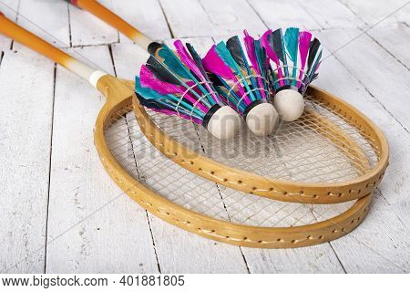 Badminton Shuttlecocks And Wooden Paddles. Accessories For Amateur Games On A Wooden Table.